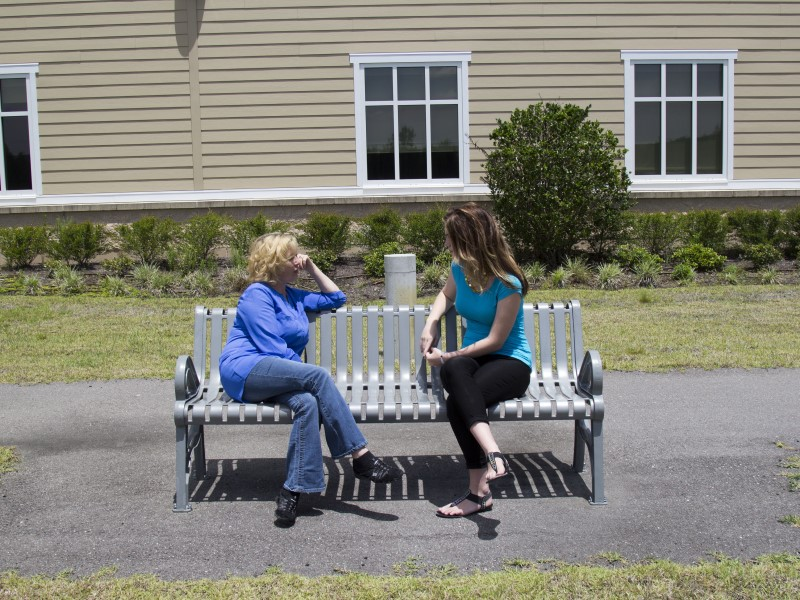 Two people sit and speak on a bench outdoors