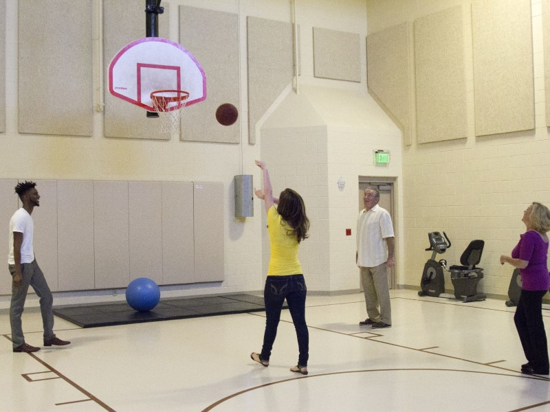 Four people play basketball on an indoor court